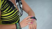 pulseira : Fitness woman using smart watch on bicycle training in sport club. Sport woman setting fitness bracelet at cardio training on static bike in gym Stock Footage