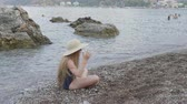 zařvat : Excited girl sitting on beach and raising hands with hat. Beautiful emotional teenage girl in hat and sunglasses sitting on beach and screaming during summertime Dostupné videozáznamy