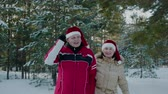 babbo natale : Winter couple in Christmas hat walking on snowy forest. Couple in love man and woman walking on snowy woodland at winter vacation. New Year Santa walks in forest