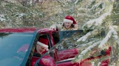 babbo natale : Cheerful man in red Christmas hat like Santa Claus waving hand from car in snowy forest. Happy couple in New Year hat in winter forest on snowy trees landscape