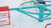 cep : Girl spinning on carousel in playground at winter. Girl riding carousel swing and losing wallet from pocket on snowy children playground