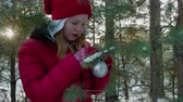 bombki : Girl hanging xmas ball on pine tree branch in winter forest. Beautiful happy teenage girl decorated evergreen tree with shiny christmas bauble in winter forest