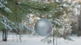 snowfall : Close-up view of rotating shiny christmas ball in winter forest. Cropped shot of woman touching silver xmas bauble hanging on tree branch in winter forest