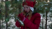 bombki : Adorable girl hanging christmas ball on pine tree in forest. Beautiful happy girl walking on snow in forest and decorating evergreen tree with shiny silver xmas bauble Wideo