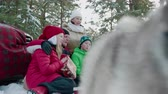weihnachtszeit : Happy family with gifts and dog in beautiful winter forest. Happy parents with son and daughter sitting together, holding christmas presents and looking away in winter forest