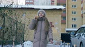 krem : Young girl in hat and coat eating ice cream on winter walk in snowy city. Cheerful girl teenager walking in winter city and eating ice cream Wideo