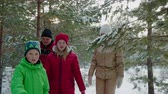 conto : Friendly family mom, dad, son and daughter walking in coniferous forest at winter holiday. Happy family walking in winter woodland through snowy coniferous trees