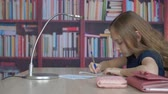 estante : Student girl writing by pen on paper sheet on bookcase background. Girl teenager girl doing homework in home office on bookshelf background in library room