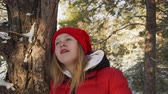nőiesség : Portrait young woman in red hat and coat in winter forest on snowy trees background. Close up face teenager girl looking up in snowy woodland at winter walk Stock mozgókép
