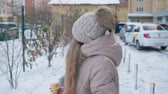 krem : Girl walking on street and eating ice cream at wintertime. Beautiful teenage girl walking on snow-covered urban street and looking over shoulder