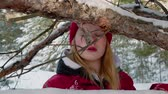 wanten : Girl peeking behind snow-covered branches in forest. Beautiful teenage girl in red hat and mittens standing behind tree twigs in winter forest