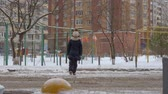 po celé délce : Pensive girl slowly crossing road in city at wintertime. Full length view of cute girl in winter outfit walking on street and crossing road during daytime Dostupné videozáznamy