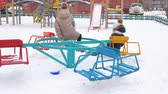 zatáčka : School girls turning on carousel swing on snowy playground at winter vacations. Teenager girl friends riding on merry go round on children playground at winter walk Dostupné videozáznamy