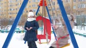 zatáčka : Teenager girl swinging on snowy playground at holiday vacations in winter city. Happy girl friends swinging on swing on children playground at winter walk
