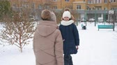 tenue : Adorable happy girls meeting outdoors at wintertime. Cute cheerful teenage girls with smartphone and wallet meeting and hugging outdoors and snowy winter day Vidéos Libres De Droits