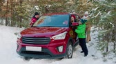 mrożonki : Family pushing red car stuck in snow in winter forest. SUV car stuck on snowy road through winter woodland. Family pulling car from snow Wideo