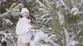 stojící : Beautiful smiling woman standing in snow-covered winter forest. Cheerful middle aged woman standing between evergreen trees covered with snow in scenic forest at wintertime Dostupné videozáznamy
