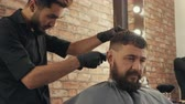 manto : Barber shaving hair of male client with electric clipper. Young male barber grooming handsome bearded client in barber shop