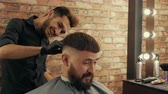 erőszakos : Happy bearded man talking with hairdresser in barbershop. Smiling young barber grooming handsome cheerful client in barber shop Stock mozgókép