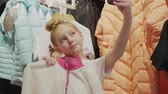 качество : Stylish girl teenager taking mobile selfie with new clothes in shopping center. Fashion teenager girl posing for selfie photo with new clothes in showroom. Young woman shopping in mall