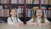 pero : Cute happy schoolgirls sitting at desk and laughing in classroom. Adorable cheerful schoolchildren holding pens and having fun while sitting at table in library Dostupné videozáznamy