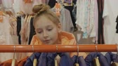 качество : Cute teenage girl looking at hangers with stylish clothes in fashion boutique. Beautiful teen girl choosing fashionable trendy clothes in shopping mall