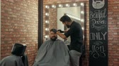 erőszakos : Hairstylist cutting hair to handsome client in barbershop. Young barber holdign scissors and grooming handsome beraded male client in barber shop Stock mozgókép