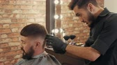 erőszakos : Barber cutting hair to bearded male client in barbershop. Hairdresser holding scissors and grooming handsome client in barber shop