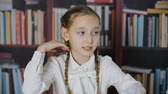 rood haar : Portrait nervous confusion schoolgirl on bookshelf background in class room. Panic and fear emoji of school girl on bookcase background in class room talking on lesson Stockvideo