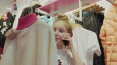 Teenager girl choosing clothes and talking mobile at shopping in fashion showroom. Shopper girl looking clothes in shop. Girl teenager calling in clothes store