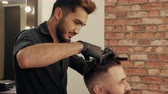 Young man getting stylish hairdo in barbershop. Haircutter combing hair and cutting hair with hairdressing scissors in male salon. Hairdresser cutting wet male hair Stok Video