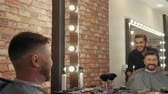 erőszakos : Smiling hairdresser and client looking at mirror. Satisfied cheerful mature man examining new haircut. Male beauty concept
