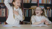 Schoolgirls having fun together on school lesson in class room. Funny teenager girl showing funny tricks with hair braids. Joyful classmates laughing on bookshelf background Stok Video