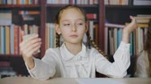 Cute school girl with braids looking to little mirror and touching hair in classroom. Portrait schoolgirl making funny faces to hand mirror in classroom Stok Video