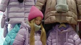 věnování : Teenager girl trying down jacket in clothes boutique at shopping. Happy young girl showing new down jacket in shopping store. Youth shopping in showroom Dostupné videozáznamy