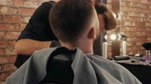 Track in dolly shot. Barber shaving beard to bearded man with electric razor in male salon. Hipster man getting trimming beard with shaver in barber salon. Stylish shaving man with trimmer Stok Video