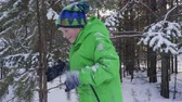 coberto : Boy playing with pine tree branch in winter forest. Adorable cheerful child standing under falling snow in beautiful winter forest Vídeos