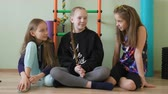 trio : Teenager girls sitting on floor in school gym. School girl friends talking together in gym Stock Footage