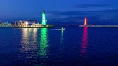establishing shot : Entrance to the harbor with green and red lighthouses and boat crossing the marinas aquatoria by night.  Stock Footage
