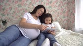 rozmnožování : young pregnant Asian woman with her little daughter have fun playing with tablet on the bed
