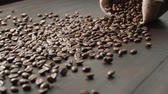 fabricado cerveja : quality of grain roasted coffee to spill from a jute bag on wooden table, slow motion Stock Footage