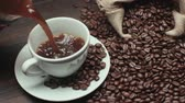 mug : pouring a Cup of hot coffee and roasted coffee beans on the table, slow motion