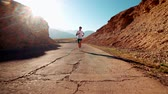 suíça : young Asian man Jogging along the old mountain road, healthy way of life, the sun glare, slow motion