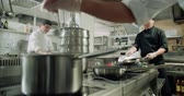 wok dishes : backstage workflow in the kitchen of the restaurant, the team of Asian chefs work with vegetables, cooking vegetarian dishes Stock Footage