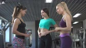saúde : three women chat in the gym friendship successes to boast a thin waistline