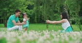 улов : young Asian family with a year-old girl in the Park teach your child to do first steps, slow motion,