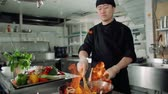 flambe : chef works mixed colored roasting vegetables in the wok-tossing and flames , kitchen Asian restaurant, slow motion