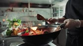highdef : close-up of a chef working the wok with flames roasting mixed colorful vegetables tossing them , restaurant kitchen , slow motion