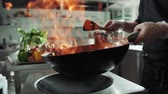 stirfry : close-up of a chef working the wok with flames roasting mixed colorful vegetables tossing them , restaurant kitchen , slow motion