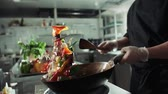 tossing : Asian chef works coloured mixed roasting vegetables in the wok with flame , kitchen Asian restaurant, slow motion